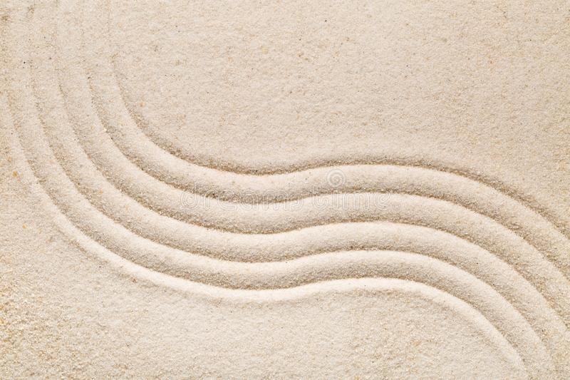 Zen sand and stone garden with raked lines, curves and circles. Zen sand garden with raked curved lines. Simplicity, concentration or calmness abstract concept royalty free stock photo