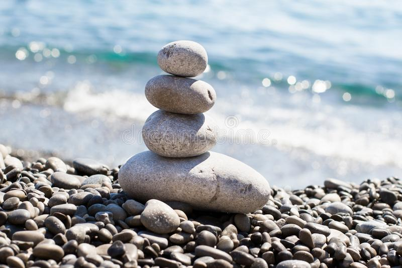 Zen sea stones pebbles stacked in a pyramid on sea coast stock image