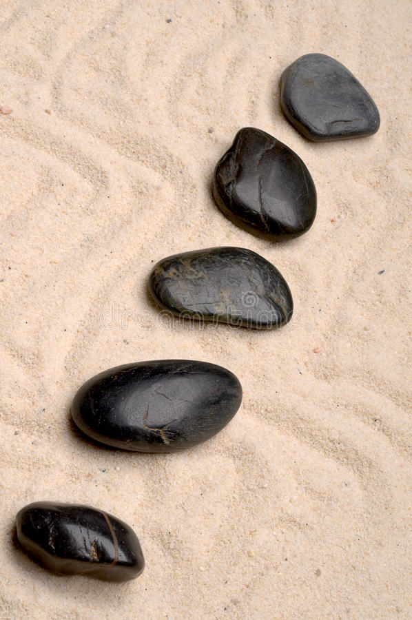 Zen spa river rocks on sand. Zen spa river rocks arranged on sand stock image