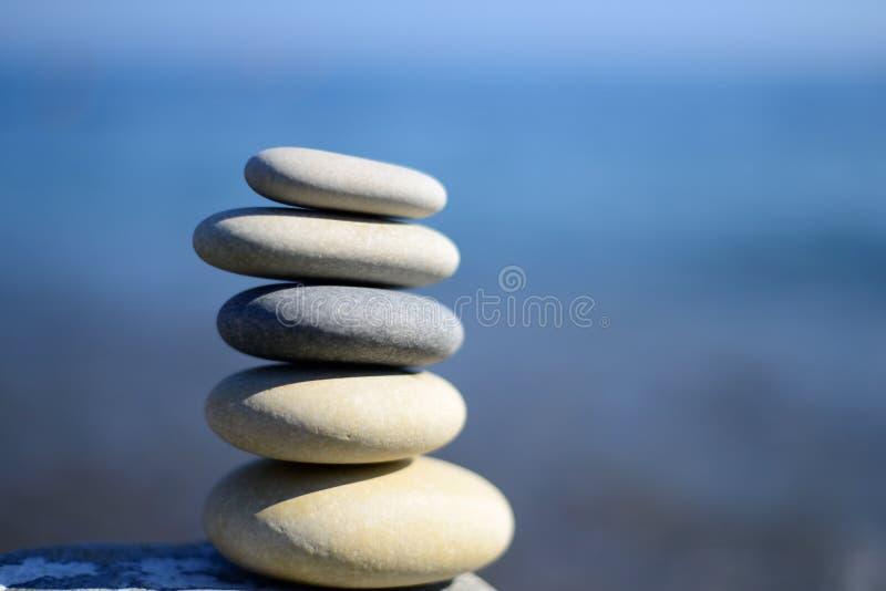 Zen spa stenen met blauwe water en hemel Achtergrond van energie de Gloeiende Cirkels met tekstruimte Saldo van stenen royalty-vrije stock afbeelding