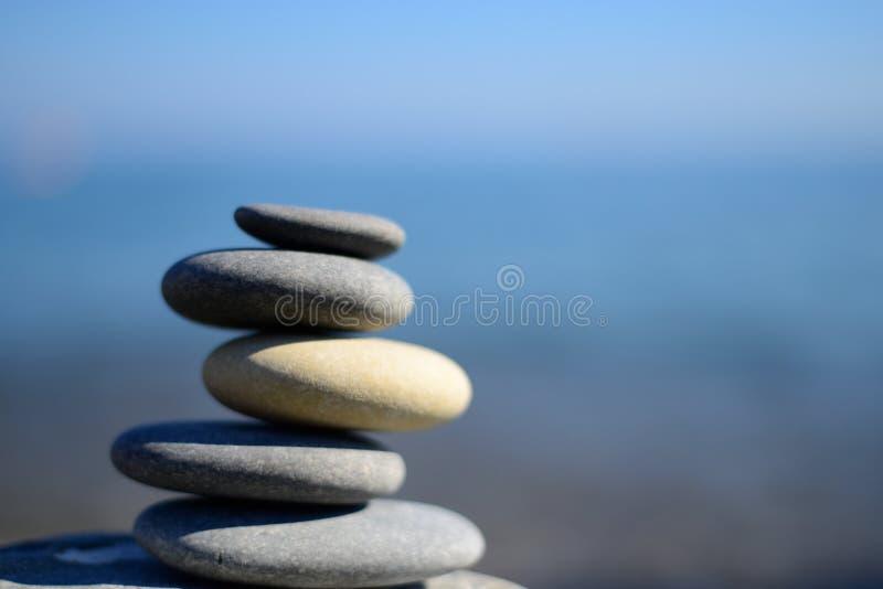 Zen spa stenen met blauwe water en hemel Evenwichtige stenenachtergrond met exemplaarruimte Kuuroordsymbool royalty-vrije stock fotografie