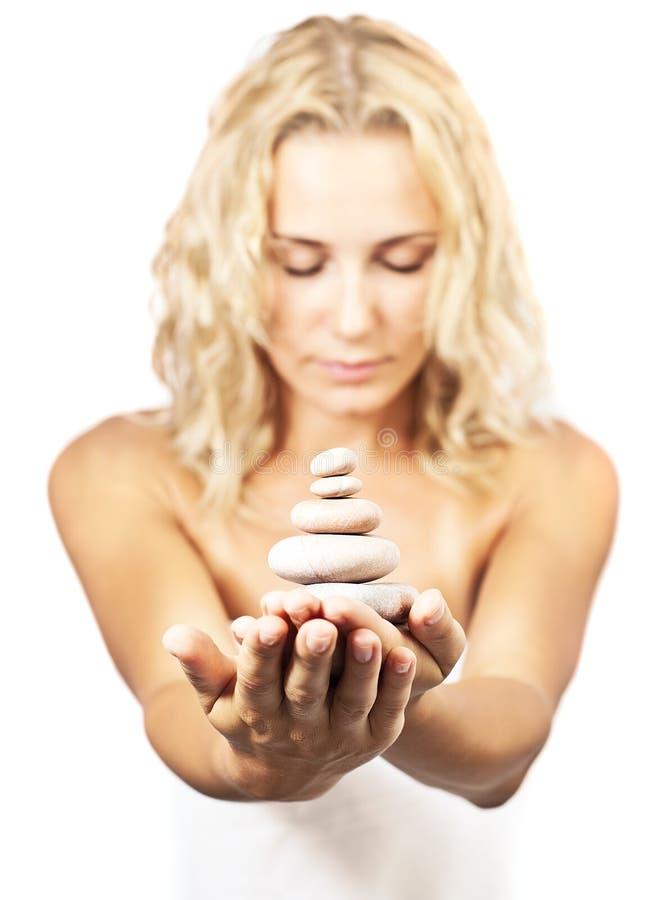 Zen spa stenen in vrouwenhanden stock afbeelding