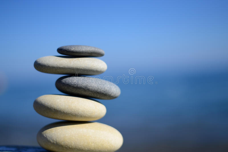 Zen spa stones with blue water and sky. Balanced stones background, copy space. Spa symbol. Balancing stones. Symbol of stability. stock photo