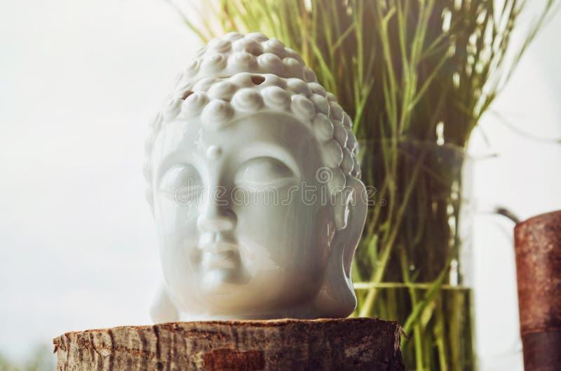 Zen spiritual ritual meditating white face of Buddha, brown candle on green floral background. Religion concept stock photos