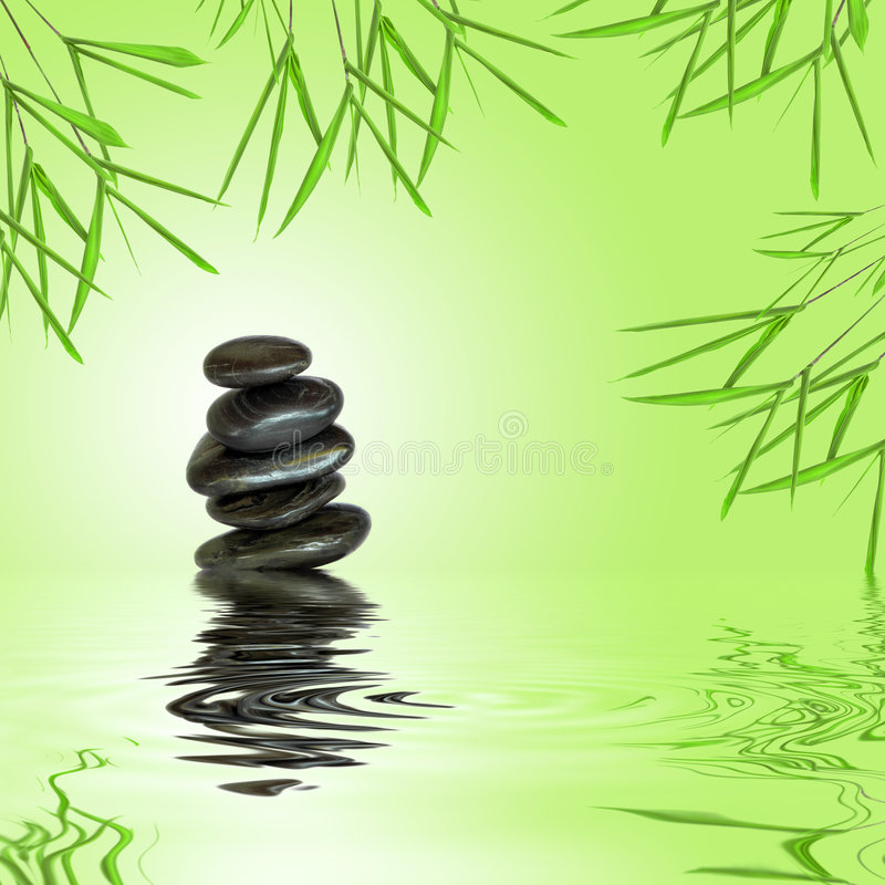 Zen Stability. Zen garden abstract of black spa massage stones in perfect balance with bamboo leaf grass and reflection over rippled water, against green royalty free stock images