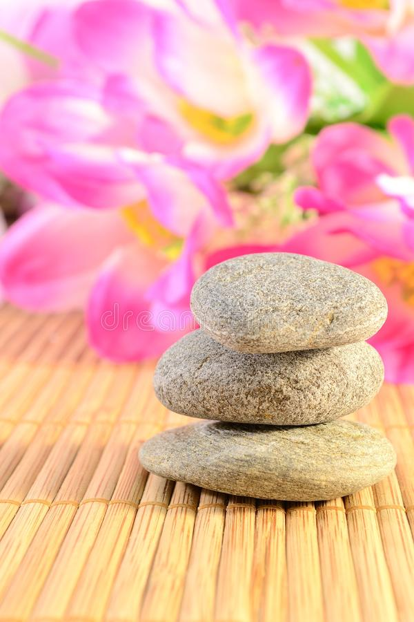 Zen stones. Balanced grey zen stones on a bamboo mat and flowers .Spa and massage concept royalty free stock image