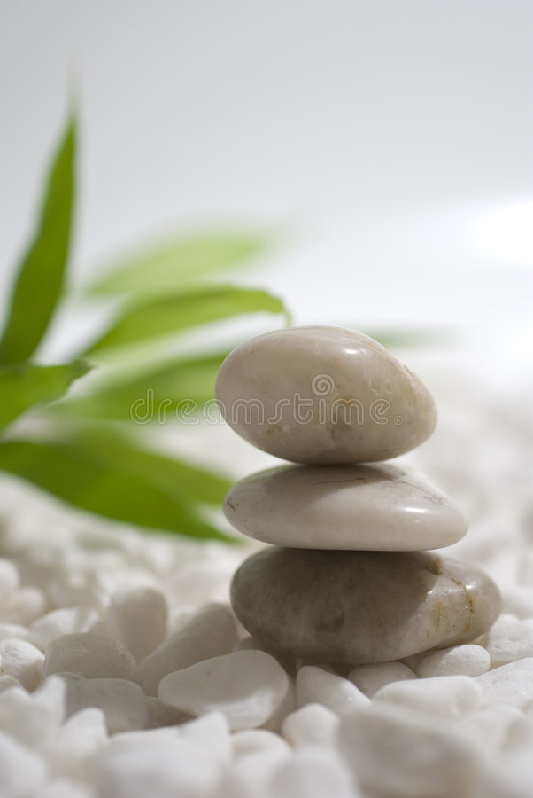 Zen stones and bamboo. On white pebbles background - meditation concept stock photography