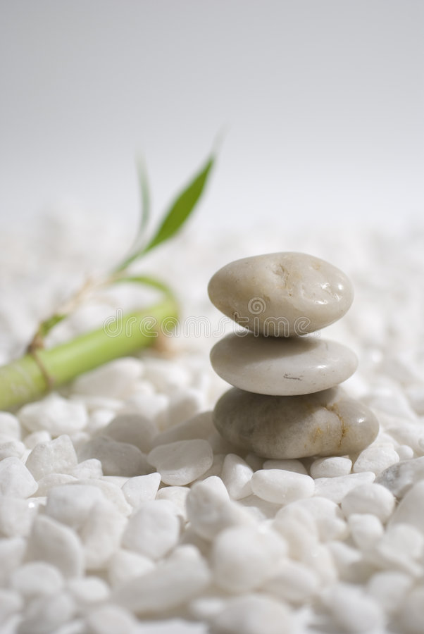 Zen stones and bamboo. On white pebbles background - meditation concept royalty free stock photos