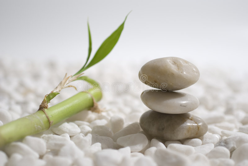 Zen stones and bamboo. On white pebbles background - meditation concept stock photo