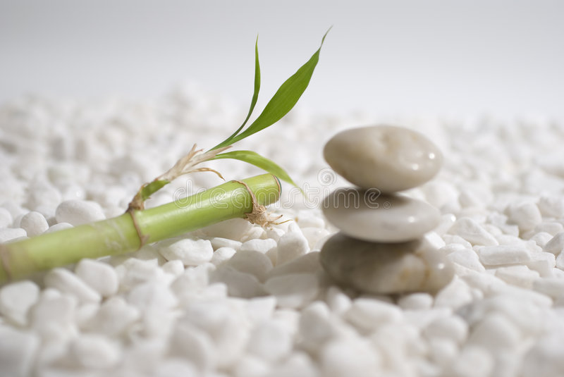 Zen stones and bamboo. On white pebbles background - meditation concept royalty free stock images