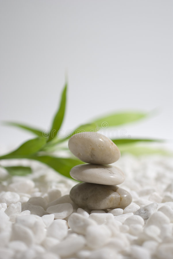 Zen stones and bamboo. On white pebbles background - meditation concept stock image