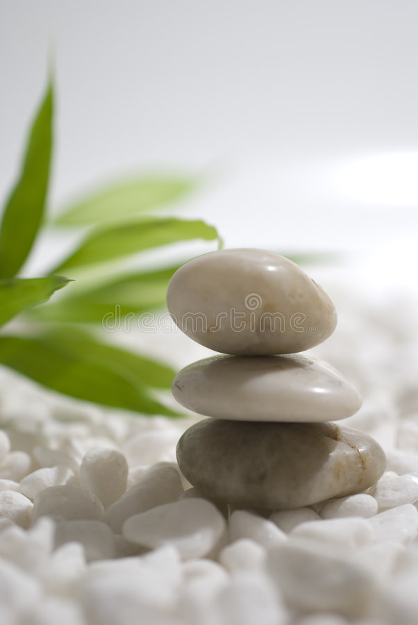 Zen stones and bamboo. On white pebbles background - meditation concept royalty free stock photography