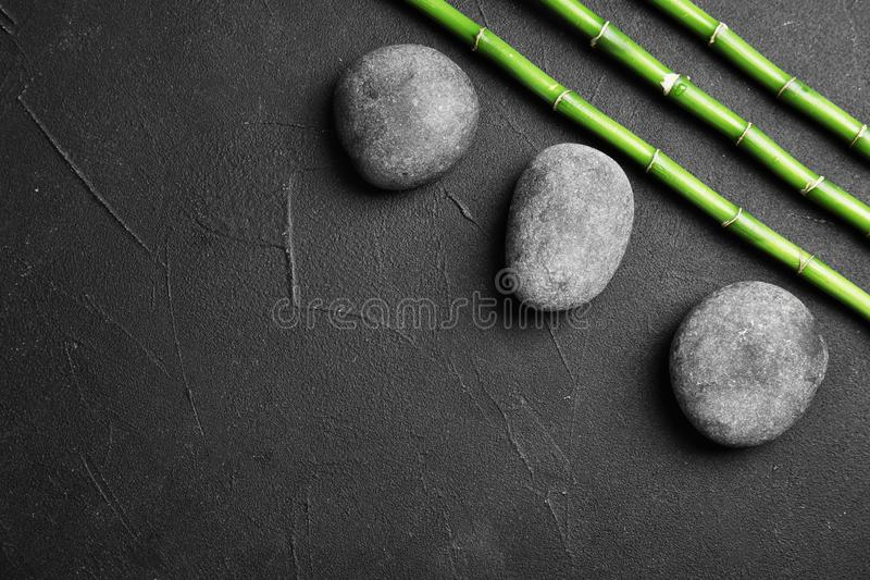 Zen stones and bamboo on dark background, top view. With space for text royalty free stock photography
