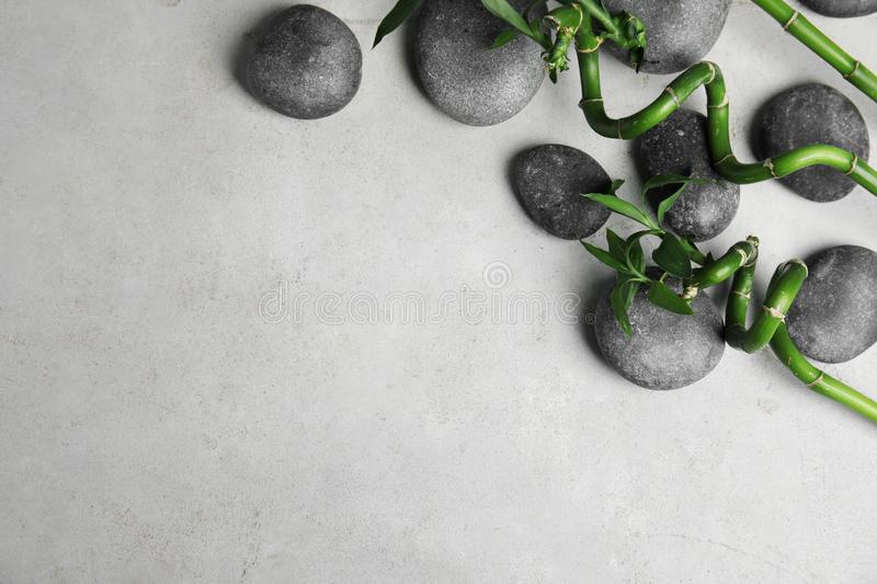 Zen stones and bamboo on grey background, top view. With space for text stock image