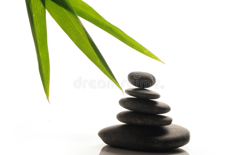 Zen stones with bamboo leaf. Zen stones row with green bamboo leaf / spa and zen concept image royalty free stock photo