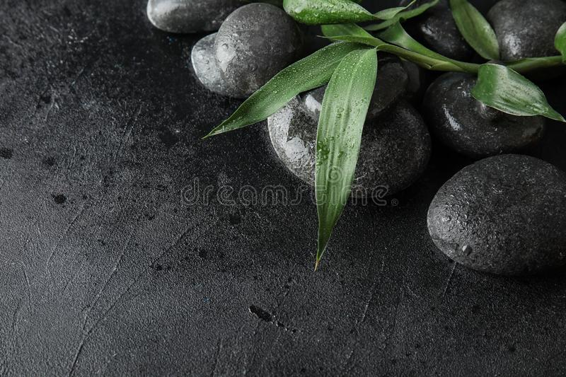 Zen stones and bamboo leaves on black, closeup. Space for text. Zen stones and bamboo leaves on black background, closeup. Space for text royalty free stock photo