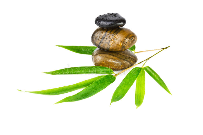 Zen stones with bamboo leaves isolated on white. Background royalty free stock photography