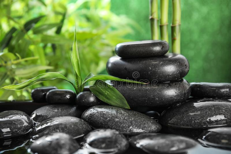 Zen stones and bamboo leaves in water on blurred background. Space for text royalty free stock photography