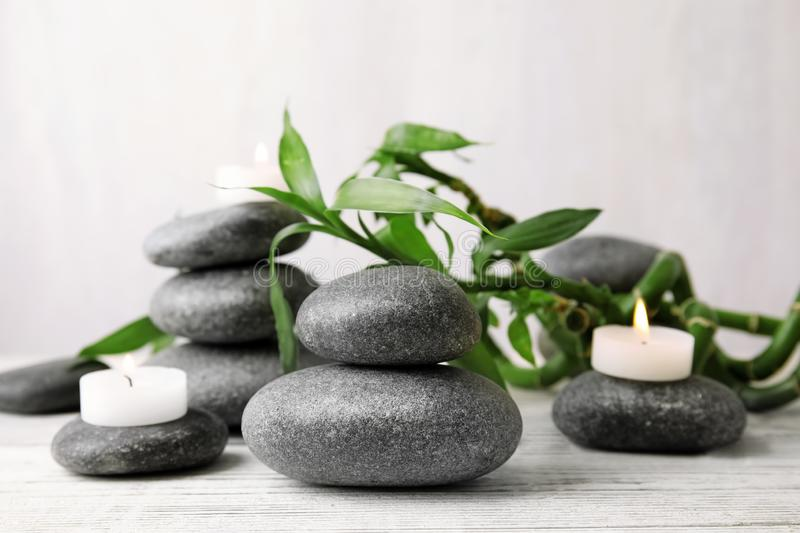Zen stones, bamboo and lighted candles on table. Against light background royalty free stock photos