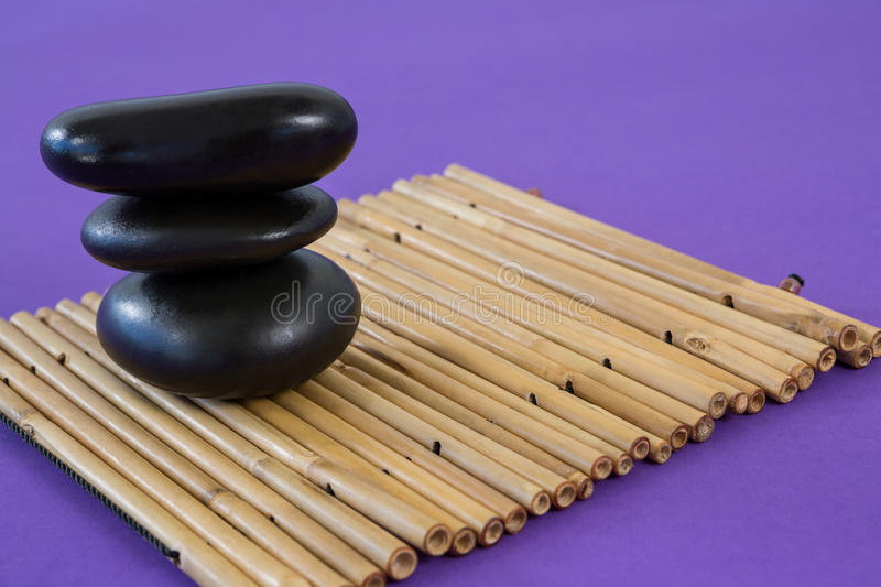 Zen stones on bamboo mat. Stacked zen stones on bamboo mat royalty free stock images