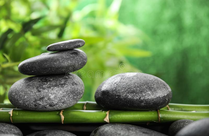 Zen stones on bamboo. Against blurred background stock images