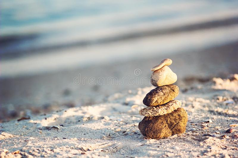 Zen Stones on beach for perfect meditation. Calm zen meditate background with rock pyramid on sand beach symbolizing stability, ha stock photo