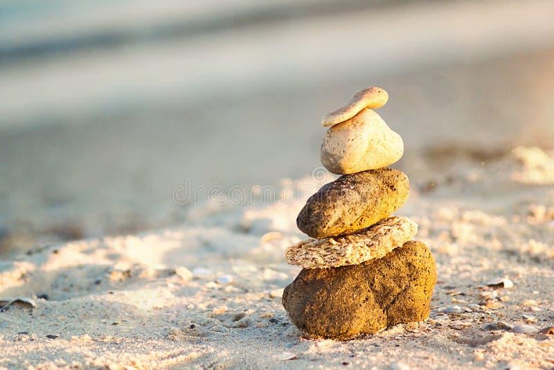 Zen Stones na praia para a meditação perfeita O zen calmo medita o fundo com a pirâmide da rocha na praia da areia que simboliza  fotografia de stock royalty free