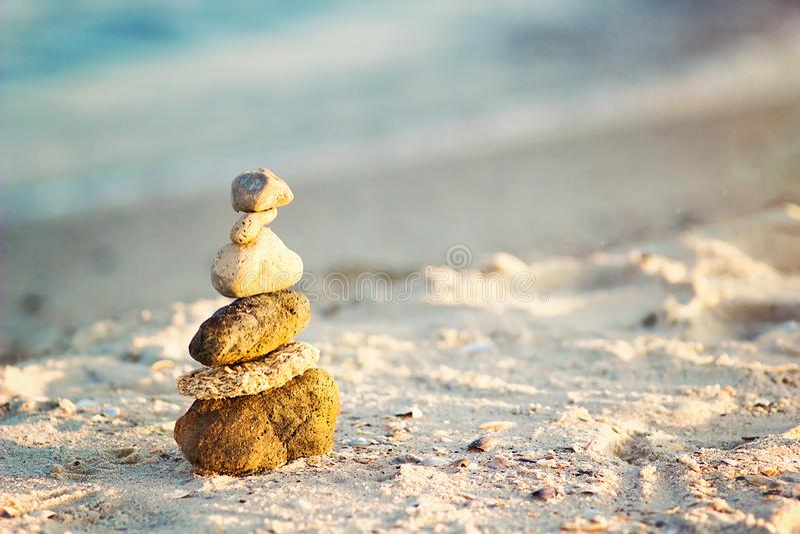 Zen Stones na praia para a meditação perfeita O zen calmo medita o fundo com a pirâmide da rocha na praia da areia que simboliza  imagens de stock