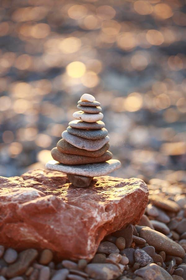 Zen Tower sulla spiaggia nella forma dell'albero di natale isolata sul fondo del bokeh della scintilla di natale fotografia stock