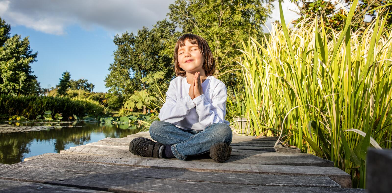 Zen young yoga child meditating alone to breathe near water stock photo