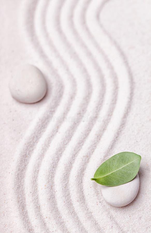 Zengarten mit einer Welle zeichnet im Sand mit einem entspannenden weißen Stein stockbild