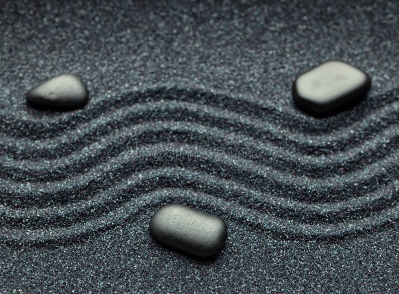 Zengarten mit einer Welle zeichnet im Sand mit entspannenden Massagefelsen stockbild