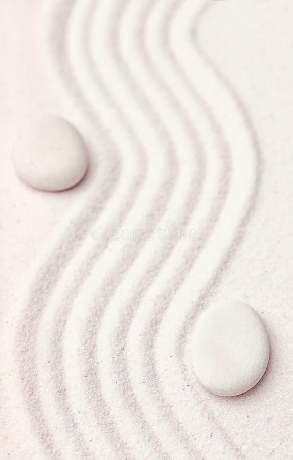 Zengarten mit einer Welle zeichnet im Sand mit entspannenden weißen Felsen stockbild