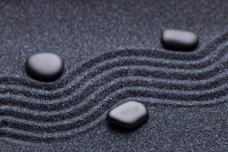 Zengarten mit einer Welle zeichnet im Sand mit iregular Steinen lizenzfreie stockfotos
