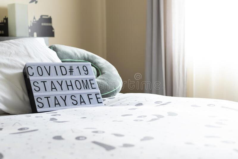 Zenithal picture of a light box with a message with a sofa behind. Coronavirus advise.Keep calm message.Stay home. Zenithal picture of a light box with a message royalty free stock photos