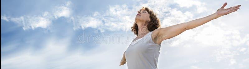 Zenmitte alterte die Yogafrau, die ihr chakra, Fahne erschließt stockfoto