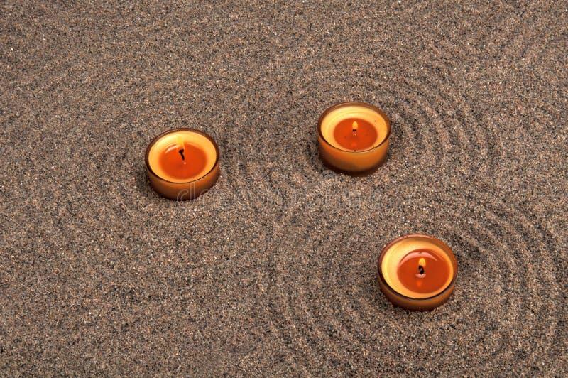 Zensammansättning Stearinljus i sanden Lugna modeller på sanden royaltyfria foton