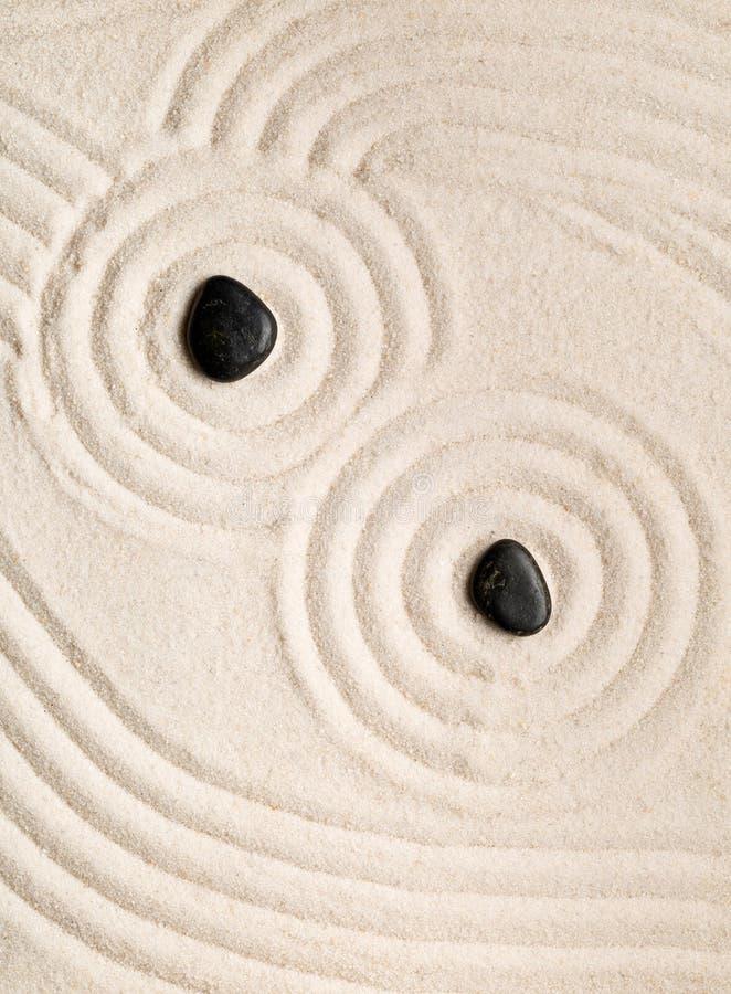 Zensand und -stein arbeiten mit geharkten Linien, Kurven und Kreisen im Garten stockbild