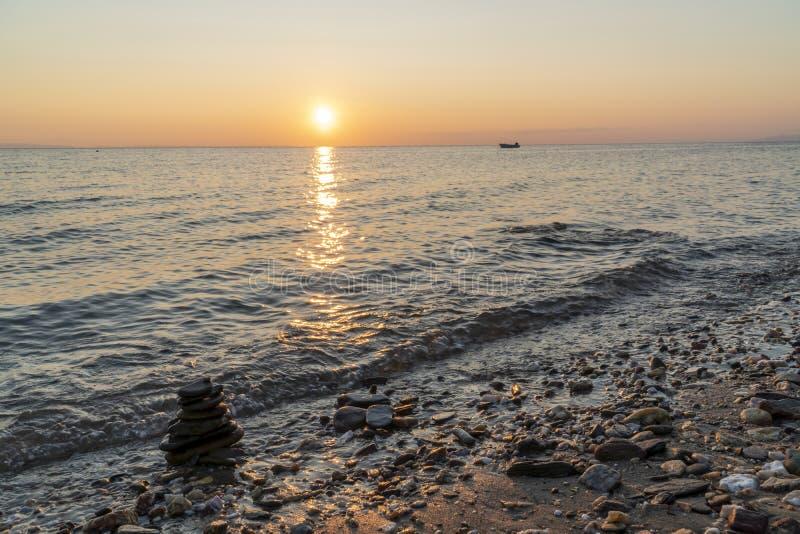 Zenstapel av stenar i havet vid solnedgång royaltyfri fotografi