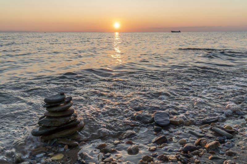 Zenstapel av stenar i havet vid solnedgång royaltyfri foto