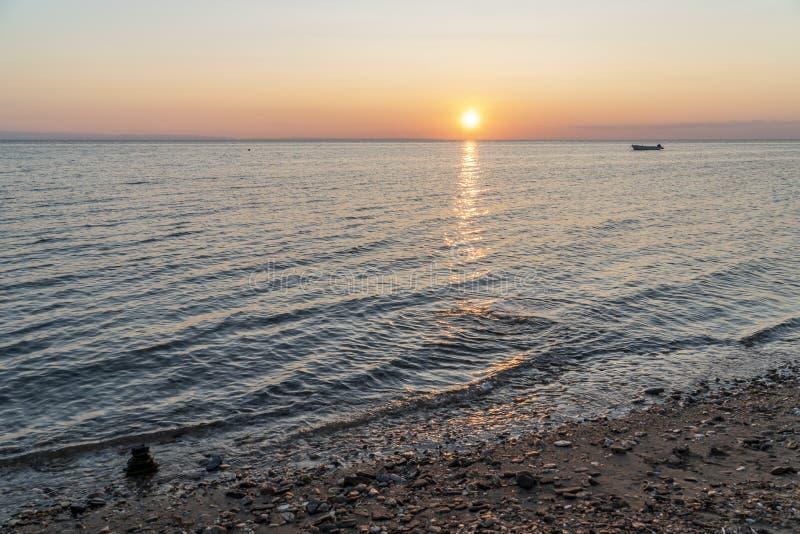 Zenstapel av stenar i havet vid solnedgång royaltyfria bilder