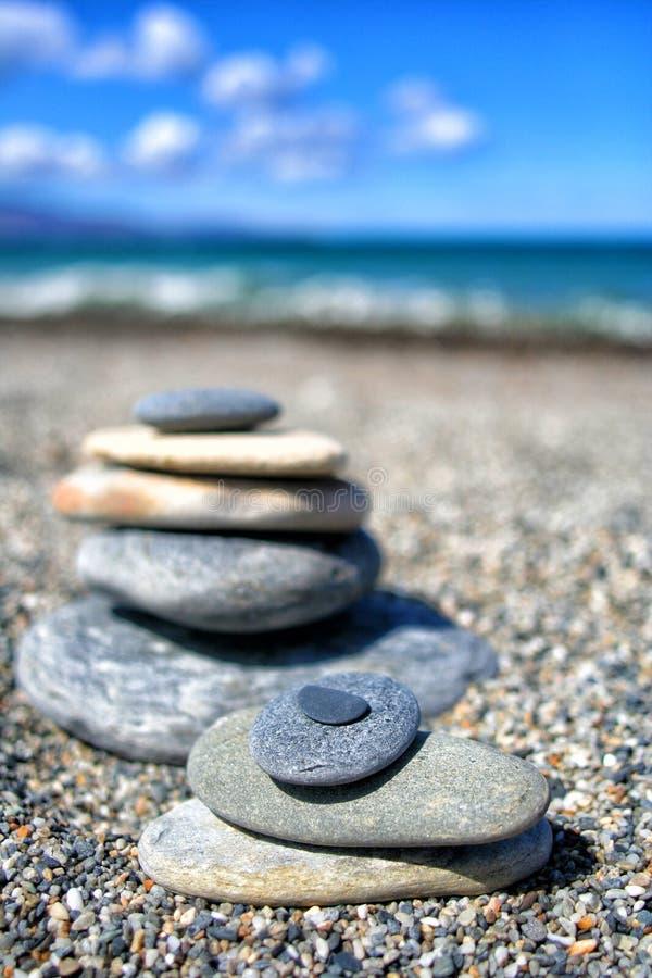 Zenstenar balanserar på stranden för perfekt meditation arkivbilder