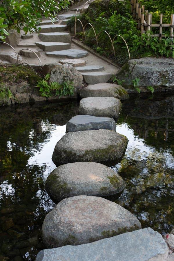 Zenstenbana i en japansk trädgård över ett stillsamt damm i Ok royaltyfri fotografi
