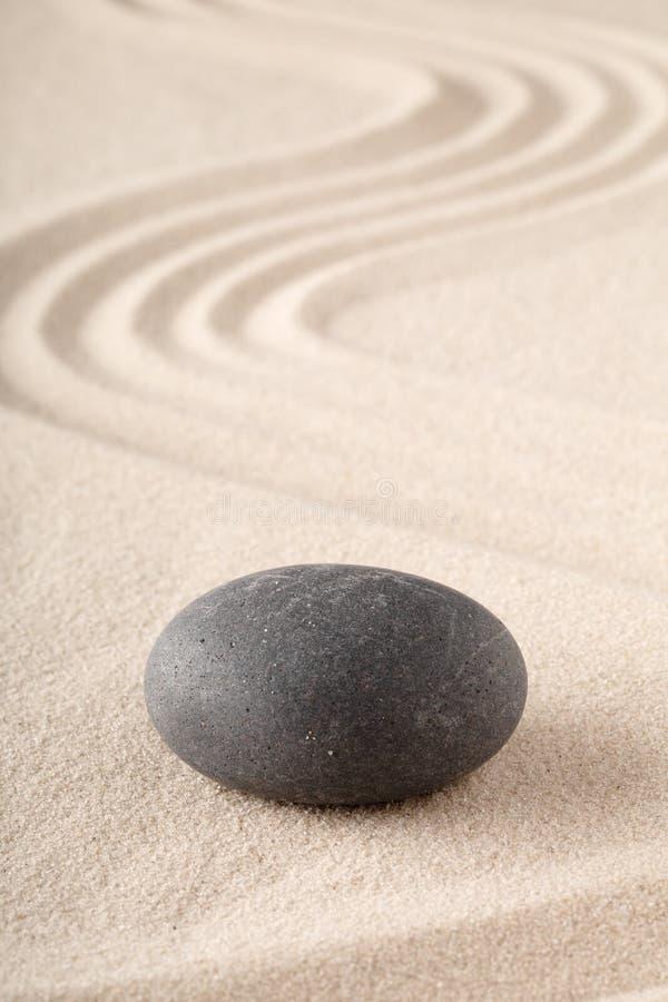 Zenträdgård med krattad sand och den runda meditationstenen för koncentration och fokus royaltyfri fotografi