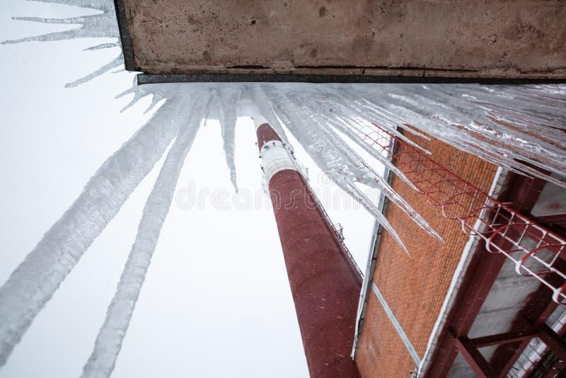 Zentralheizung und Kraftwerk mit Rauchfabrikschornstein und -eiszapfen auf dem Dach stockfotografie
