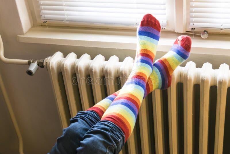 Zentralheizungsheizkörper und -frau in gestreiften Socken lizenzfreie stockfotos