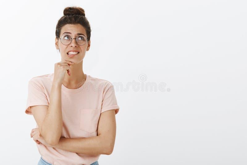 Zenuwachtig onzeker en unconfident jong slim Europees wijfje die in glazen en haarbroodje onhandig en ongerust gemaakte tanden di stock foto