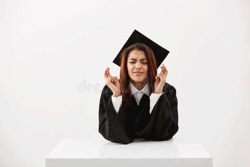 Zenuwachtige Afrikaanse student die haar die diploma, met vingers hopen te krijgen over witte muurzitting bij lijst worden gekrui stock foto's