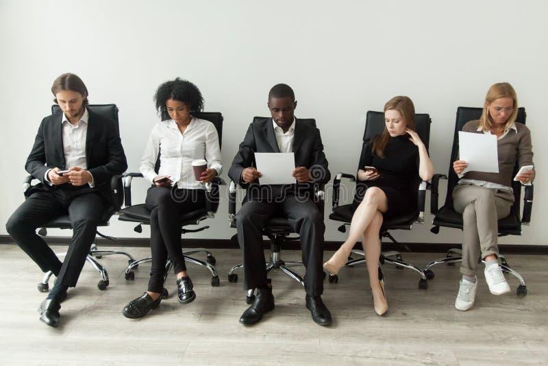 Zenuwachtige beklemtoonde baankandidaten die voor gesprekswachten voorbereidingen treffen stock foto's