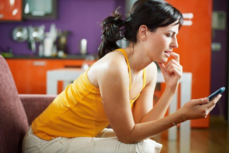 Zenuwachtige cellphone van de vrouwenholding stock afbeelding